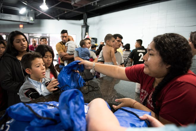 A volunteer with Catholic Charities Respite Center in McAllen, Texas, gives migrants recently released from border patrol hygiene kits on June 27, 2019.