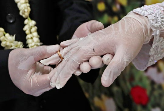 Wearing latex gloves to prevent the spread of the coronavirus, bride Elma Diyani, right, and groom Octavianus Kristianto exchange rings during their wedding ceremony at the local Religious Affairs Office in Pamulang, on the outskirts of Jakarta, Indonesia, June 19, 2020.