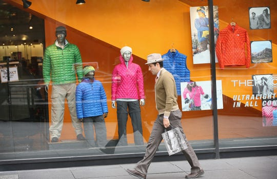 A shopper in 2013 walks past a window display at a North Face store in Chicago. The North Face said Friday it would stop advertising in the U.S. on Facebook until the social network stops the flow of hate speech on its platform.