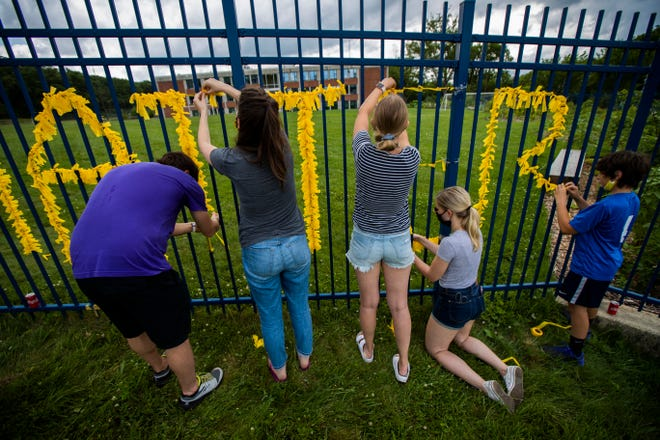 """Teachers from Capital City Public Charter School in Northwest Washington and others decorate their school fence with yellow paper to spell the words Black Lives Matter on June 18, 2020. In an apparent backlash against the teaching of """"anti-racism"""" lessons in schools, proposed legislation has cropped up in at least a dozen states attacking a once obscure legal premise — critical race theory, which questions how the legacy of slavery still affects American society today."""