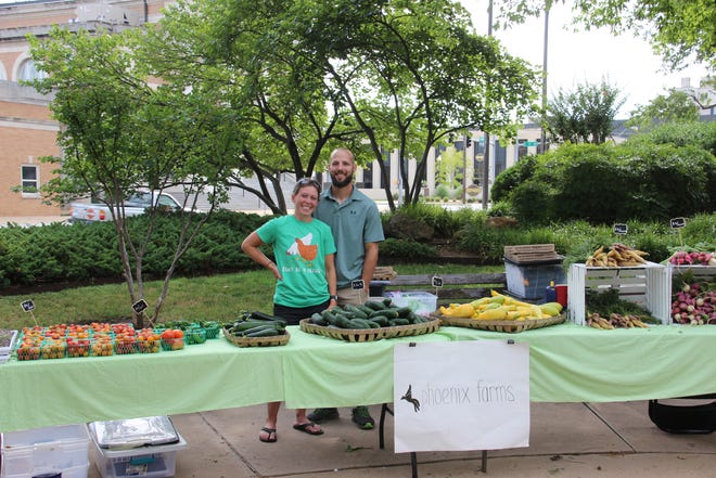 Robin Brown and her husband, Whitney Brown, stand behind their booth Saturday morning at the farmers market in Ardmore's Central Park. Robin Brown said she took over the farmers market this year after there was talk of not having it.