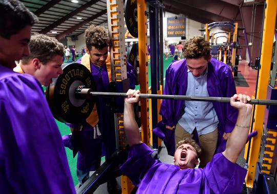 Brodey Baker playfully yells as he lifts weight on a bench press in the Doghouse athletic building Friday at Wylie High School. The 2020 graduating class retreated to the field house after a severe thunderstorm halted the evening's commencement ceremony.