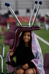Mia Hernandez takes shelter beneath a chair while watching Saturday's Wylie High School commencement. A brief rain fell halfway through the ceremony which had been forestalled from the night before when a severe thunderstorm interrupted the original graduation ceremony.