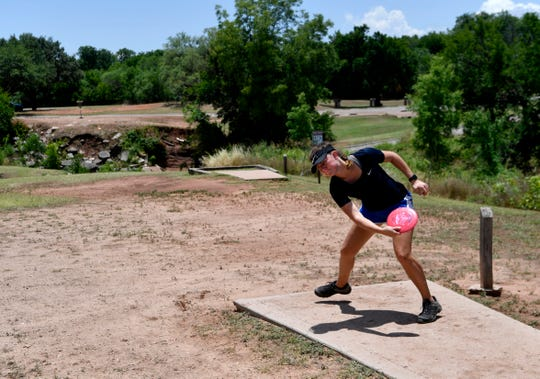 Heather Wyatt, of Abilene, tees off during the Abilene Wild Hair disc golf tournament at Will Hair Park Saturday June 20. Wyatt won the Open Women's title in one of the first Professional Disc Golf Association tournaments back following cancellations due to COVID-19.