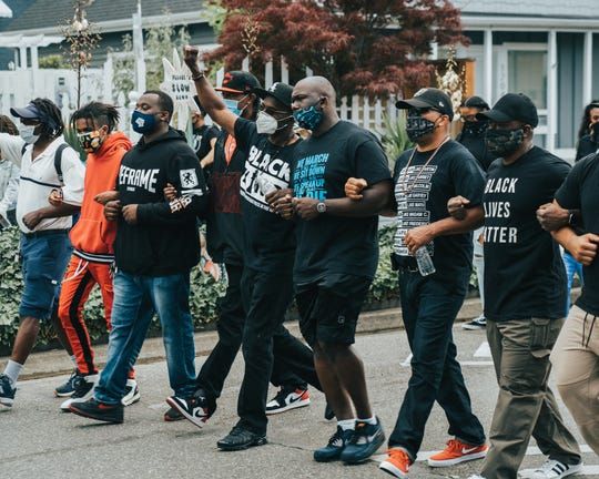 A group of men locks arms to lead the procession along Martin Luther King Jr. Way in Bremerton Saturday. The afternoon march was the second event in the city to mark the Juneteenth holiday.