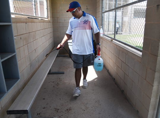 Josh Sandoval sanitizes a dugout after a game, Saturday, June 20, 2020, at the Paul Jones Avenue Sports Complex. Coaches, athletes, parents and officials were encouraged to social distance and sanitize used spaces.