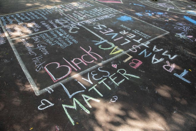 """The first Juneteenth Celebration at Inwood Park featured food, music, a voter registration table and games for kids. The event also featured speakers who spoke about how far we've come and how far we need to go. Pictured is """"Say Their Names"""" written in chalk."""