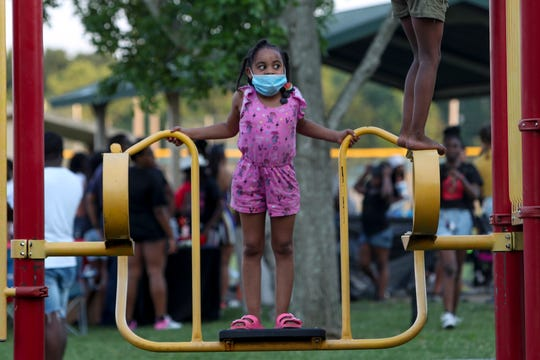 Kids play on a playground at a Juneteenth Cookout Celebration behind Kenwood Elementary in Clarksville, Tenn., on Friday, June 19, 2020.