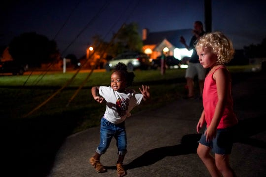 Anna Sanders, 3, left, and Kaylen Miller, 5, right, dance in the spotlight of Manny Sander's cell phone at the Sander's family Juneteenth celebration at their home on Broadmoore Drive in Clarksville, Tenn., on Friday, June 19, 2020.