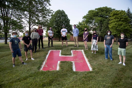 Alumni of Huron High School that trying to have the school denounce the use of Native American imagery pose for a photo outside of the high school in New Boston, Friday, June 19, 2020.