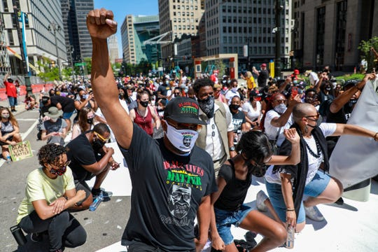 Protestors kneel on the hot concrete for eight minutes and 46 seconds, the amount of time Ex-Minneapolis Police Officer Derek Chauvin pressed his knee on George Floyd's neck as he begged for his life, during the Juneteenth BLM March on June 20, 2020.