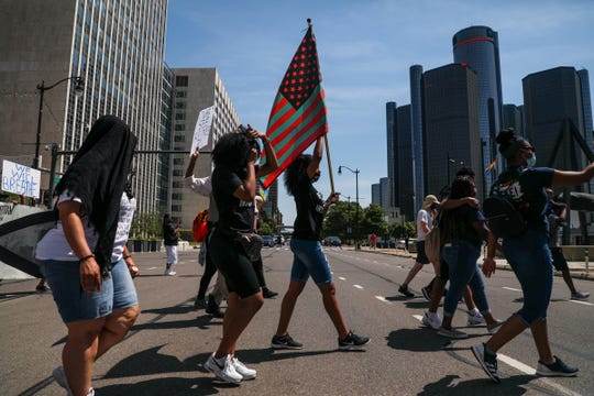 Protestors march down Woodward Avenue through downtown Detroit past Joe Louis fist monument, during the Juneteenth BLM March on June 20, 2020.