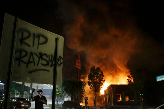 "In this  June 13, 2020 photo, ""RIP Rayshard"" is spray-painted on a sign as flames engulf a Wendy's restaurant during protests in Atlanta. The restaurant was where Rayshard Brooks was shot and killed by police the previous evening following a struggle in the restaurant's drive-thru line."