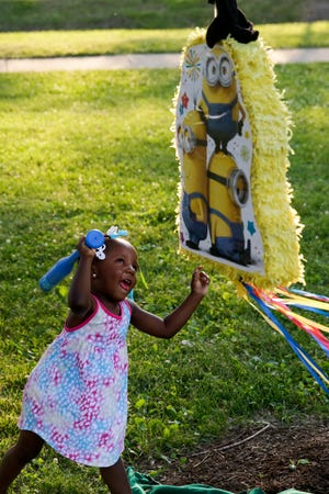 A young girl swings at a pinata during a Juneteenth celebration, Friday, June 19, 2020 at Columbian Park in Lafayette.