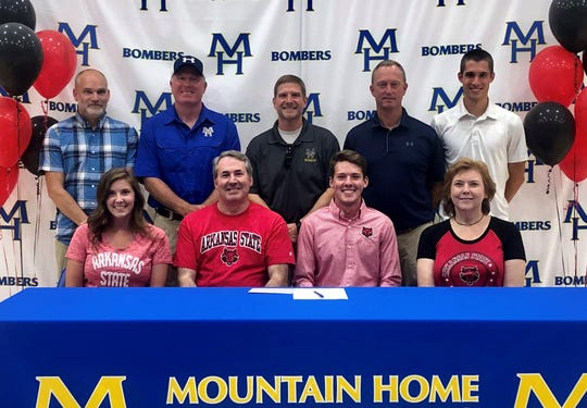 Mountain Home's Jacob Pyeatt recently signed a National Letter of Intent to run track and cross country at Arkansas State University. Pictured at Pyeatt's signing ceremony are: (front row, from left) Ashley Pyeatt, Richard Pyeatt, Jacob Pyeatt, Marianne Pyeatt; (back row) MHHS coaches Robert Blades, Clint Pevril, Philip Goodwin, Mitch Huskey and Wil Norris.