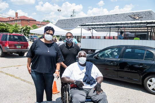 Organizers Carmen Moore-Zeigler, Orlando Cannon and Robert Wright pose for a picture as volunteers hand out food at West Alabama Jubilee Community Organization's Feeding Fathers event, sponsored by the Moore-Zeigler Group and Cannon Janitorial, on Fairview Ave in Montgomery, Ala., on Saturday, June 20, 2020.