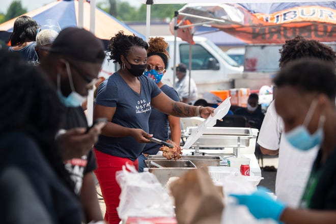 Volunteers hand out food sponsored by Moore-Zeigler Group and Cannon Janitorial on Fairview Ave. in Montgomery, Ala., on Saturday, June 20, 2020.