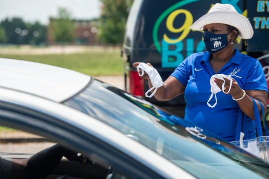 Cubie Ray Hayes hands out face masks as volunteers hand out food sponsored by Moore-Zeigler Group and Cannon Janitorial on Fairview Ave. in Montgomery, Ala., on Saturday, June 20, 2020.