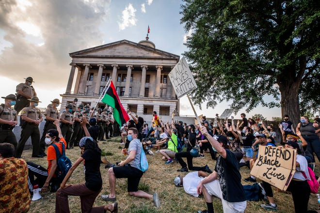 Protesters enter a space in front of state troopers on the Capitol grounds during a Defend Black Lives protest held on Juneteenth in Legislative Plaza on June 19, 2020.