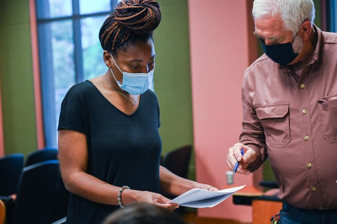 Osasere Emovon, a second-year master's student in public health, looks over consent forms from Steve Fraze, a professor and department head in the College of Agricultural, Consumer and Environmental Sciences, who will participate in a project to evaluate an automated telehealth system that monitors COVID-19 symptoms.