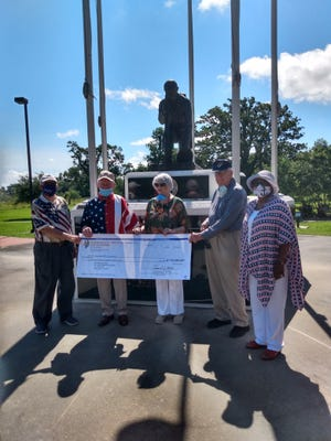 Opelousas businessman Bobby Dupre (second from left) presents a $25,000 check to help fund a visitors center at the St. Landry Veterans Memorial. Along with Dupre are, from the left, architect Jerome Gaudet, Barbara Johnson, Bill Johnson and memorial chairperson Pat Mason-Gullory.