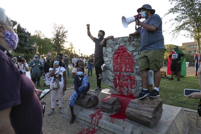 People gather at a Confederate monument to demand its removal in front of the Arizona Capitol during A March With Our Ancestors in celebration of Juneteenth in Phoenix on June 19, 2020. Juneteenth, also known as Freedom Day, marks the anniversary of the day African Americans enslaved in Galveston, Texas, learned of their freedom.