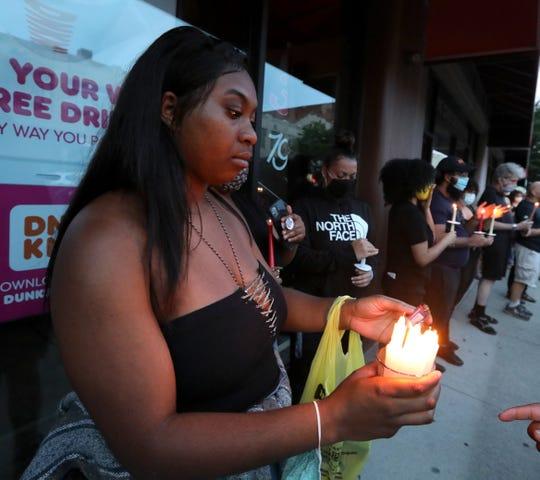 Jaiya Hewitt of Pine Bush holds candles on Main St. during a Junteenth vigil in Poughkeepsie June 18, 2020.