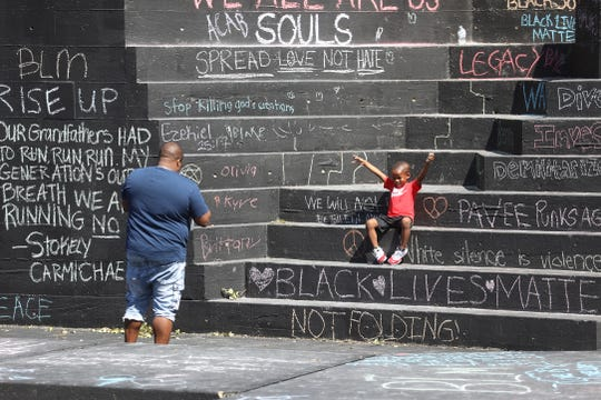 Charles Thomas of Gates photographs his son, Zaire, 4, at Martin Luther King Jr. Memorial Park among all the messages written over the past few days.