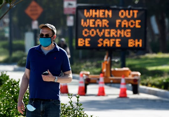 In this April 16, 2020, file photo, an electronic sign on Santa Monica Boulevard reminds people to wear masks to limit the spread of coronavirus in Beverly Hills, Calif. Gov. Gavin Newsom's administration on Thursday, June 18, 2020, mandated that Californians wear masks in most indoor settings as the state continues to battle the coronavirus.