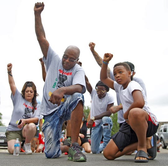 Demonstrators take a knee in honor of George Floyd during a march down Martin Luther King Drive in San Angelo during the Juneteenth holiday celebration Saturday, June 20, 2020.