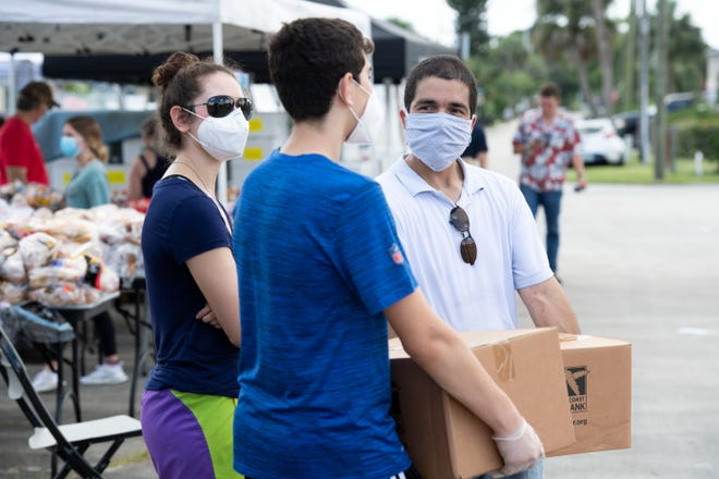 Oz Vazquez (right), of Port St. Lucie, who is challenging Rep. Brian Mast for his Congress seat, gives away food from the Treasure Coast Food Bank during the Helping Hands community event hosted by the NAACP of Martin County on Saturday, June 20, 2020, in Stuart. The event featured free food and food supplies, COVID-19 testing, educational supplies, hurricane supplies, voter registration and more.