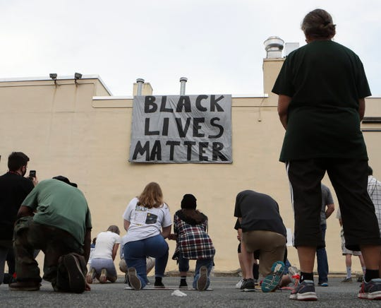 Protesters stand or kneel in silence for 8 minutes and 46 seconds at the conclusion of a march for an end to racial and social injustice Friday evening in Wilmington.