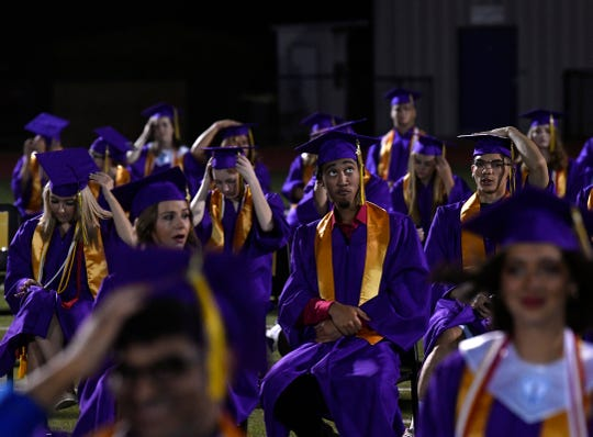 Justus Jefferson glances skyward as his fellow graduates hold onto their mortarboard hats during Friday's Wylie High School graduation. Minutes later, the ceremony was halted and students retreated to the Doghouse athletic building while the storm broke.