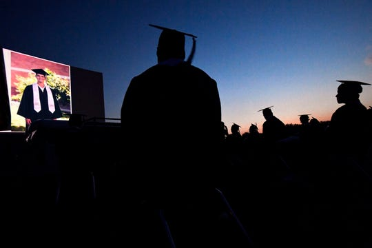 Eula High School graduates are silhouetted in the twilight as they watch the slideshow of their classmates during commencement May 22. The district rented Abilene's Town & Country Drive-In Theatre as an open-air option for graduation during the coronavirus pandemic.