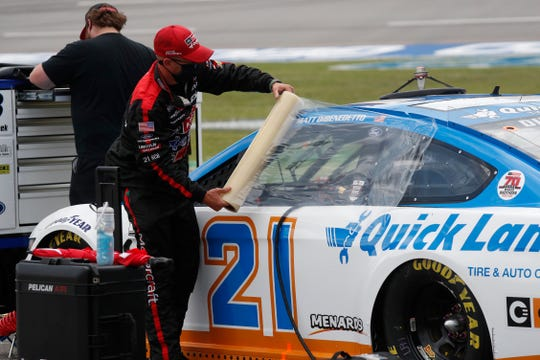 A crew member covers the car of driver Matt DiBenedetto as inclement weather rolls Sunday at Talladega.
