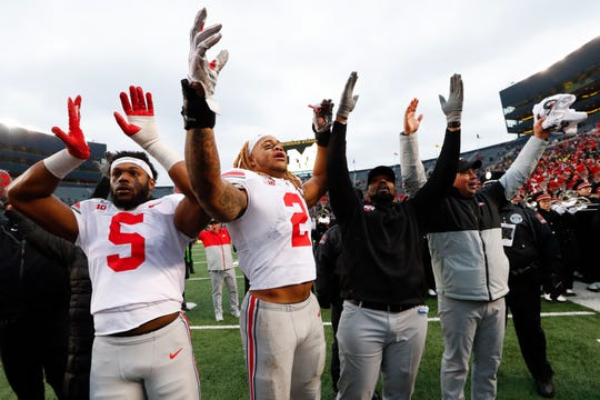 In this Nov. 30, 2019, photo, Ohio State's Baron Browning (5), Chase Young (2), linebackers coach Al Washington and head coach Ryan Day celebrate after a victory over Michigan in Ann Arbor.