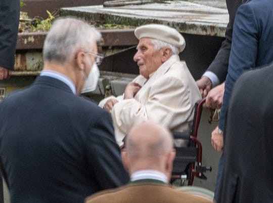 Emeritus Pope Benedict XVI is wheeled in his wheelchair as he visits the grave of his parents and sister at the Ziegetsdorf cemetery near Regensburg, Germany, Saturday, June 20, 2020.