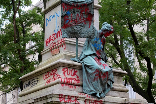 The bronze sculpture representing the Goddess of Masonry on the base of the statue of a Confederate general, Albert Pike, is seen with red paint, after protestors toppled Pike statue's and set on fire early Saturday, June 20, 2020, in Washington.