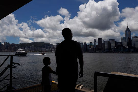 People walk at the waterfront of the Victoria Harbor of Hong Kong, Saturday, June 20, 2020.
