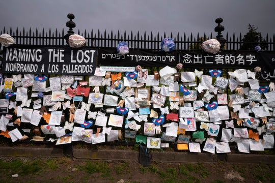 In this May 28 photo, a fence outside Brooklyn's Green-Wood Cemetery is adorned with tributes to victims of COVID-19 in New York.