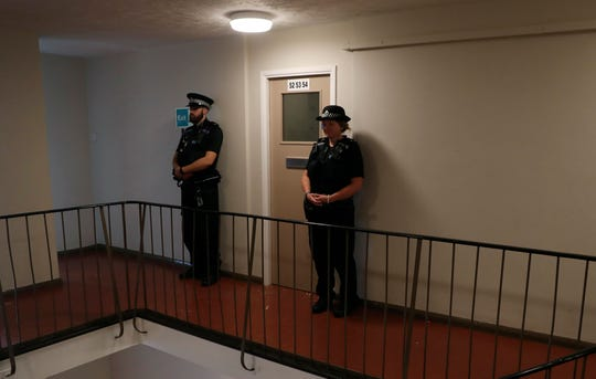 Police stand guard outside a top floor flat on Basingstoke Road that was raided by police a day after a multiple stabbing attack in Forbury Gardens, Reading, England. British police say they are treating a stabbing rampage in a park that killed three people as a terrorist attack.