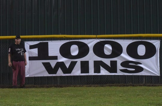 Lockeroom head coach Lester White stands next to the banner raised in centerfield at the conclusion of his 1,000th career victory Saturday night.