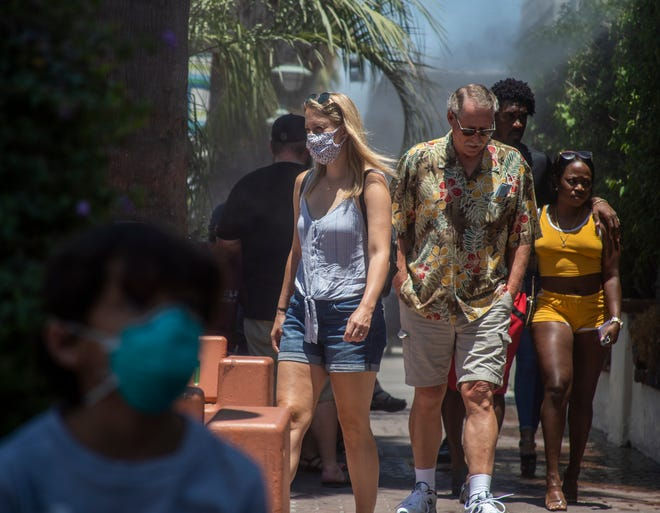 Masked and unmasked people walk in downtown Palm Springs on a Sunday afternoon in June.