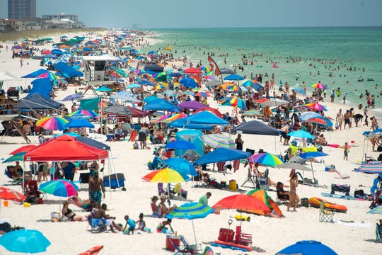 Visitors relax on the beach in Pensacola, Fla., on June 21. A trip to the vacation destination involves sun, sand and possibly a case of COVID-19.