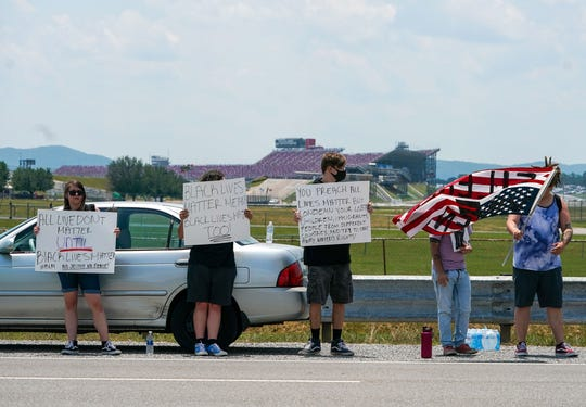 Black Lives Matter and racial justice supporters line the street outside Talladega Superspeedway to protest a parade of vehicles displaying the Confederate flag.