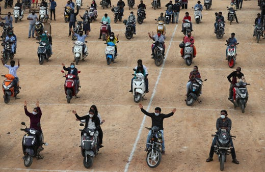 Faithful sit on their two-wheelers and pray as they attend a drive-in mass in an open area of Bethel AG Church as part of maintaining social distancing to prevent the spread of coronavirus in Bengaluru, India, Sunday, June 21, 2020. India is the fourth hardest-hit country by the COVID-19 pandemic in the world after the U.S., Russia and Brazil.