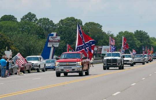Confederate flag supporters drive in a parade route down Speedway Blvd. outside Talladega Superspeedway as protesters and racial justice supporters line the side of the road.