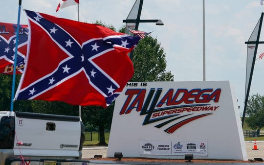 Confederate flag supporters drive by the entrance to Talladega Superspeedway on June 21, 2020 ahead of the NASCAR Cup Series GEICO 500 race.