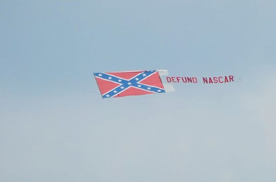 "A banner, flying behind a plane over Talladega Superspeedway on June 21 ahead of the scheduled NASCAR Cup Series race, reads: ""DEFUND NASCAR."""