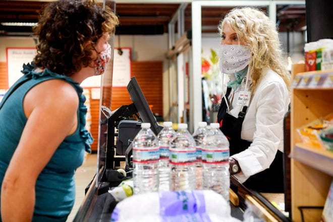 """Jennifer Murray, left, talks to Sherri Lynn Clark, a 35-year employee of Earth Fare, at the checkout counter June 22, 2020. Murray said she has been shopping at Earth Fare since 1996. """"It's a huge part of my history here in Asheville,"""" she said, """"It's such a small town, I used to do her hair."""""""